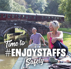 Time to Enjoy Staffs Safely. Couple on canal boat with steam train in the background.