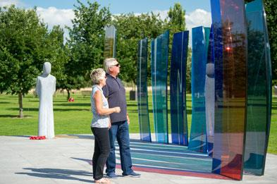 Couple reading the inscription on the Naval Services Memorial at National Memorial Arboretum