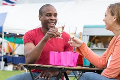 Couple seated at table drinking wine alfresco at Stone Food & Drink Festival