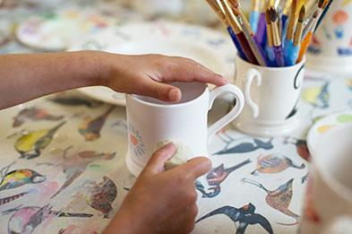 Kids decorate mugs with sponges and paint at Emma Bridgewater Factory. Photocredit:VisitBritain&DianaJarvis