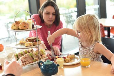 Mother and young daughter having afternoon tea at NMA restaurant