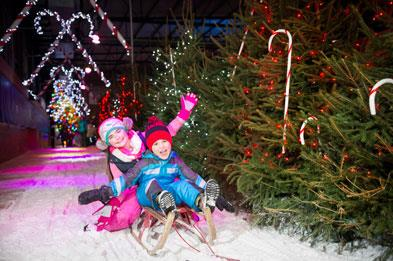 Children sledging on ice track at SnowDome for Santa's Winter Wonderland