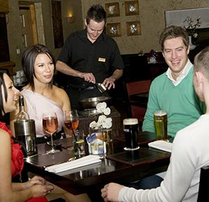 Group of friends share a joke before dinner at The Three Horseshoes, near Leek