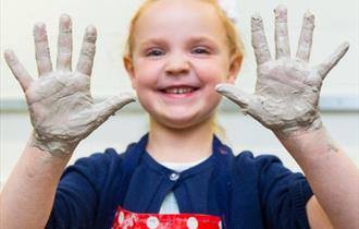 Girl with clay-covered hands